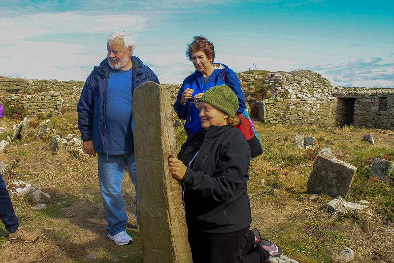Guests on Discover the North 2013 tour on Inishmurray at the fertility stone.